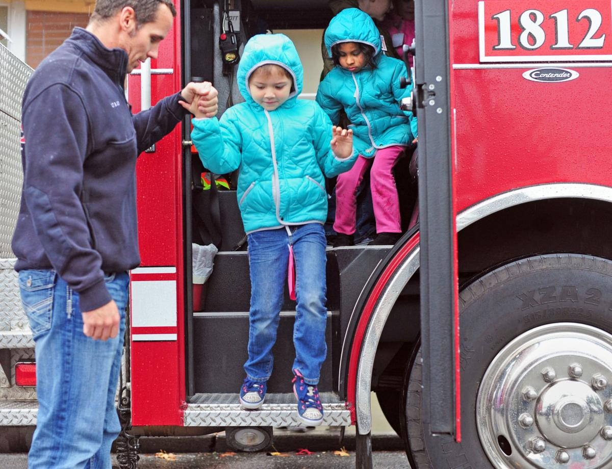 Firefighter Brad Judy helps students at Allen Elem in Bow during Operation Warm event at the school